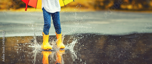 Feet of child in yellow rubber boots jumping over puddle in rain