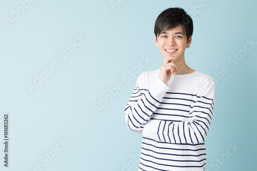Fotografie, Obraz  portrait of young asian man isolated on blue background