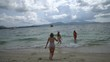 Three beautiful young happy women in bikini's enjoying their holiday on the sandy beach on tropical paradise island. One girl with selfie-stick doing photos in the water - video in slow motion