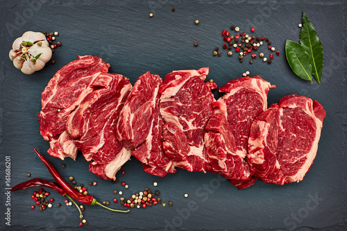 Foto  Fresh raw beef steaks with chilly pepper on black slate board