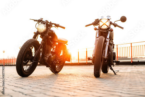 Photo Front view of two vintage custom motorbike caferacer motorcycle one with grill headlight another with tape cross on empty rooftop parking lot with backlight sun during sunset