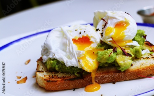 Poached egg with avocado on white plate Wallpaper Mural