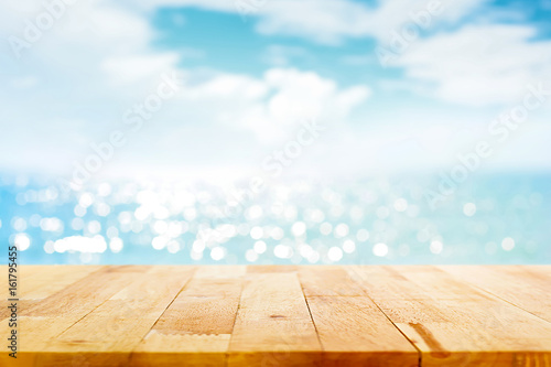 Photo  Wood table top on blur sparkling sea water and summer sky background