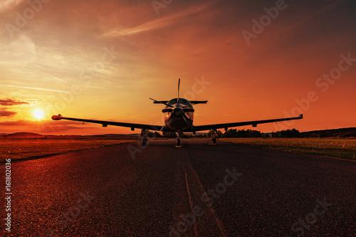 Single turboprop aircraft on evening runway. Fototapet