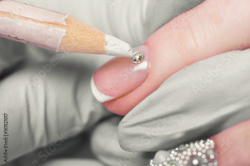 Closeup finger nail care by manicure specialist in beauty salon Poster