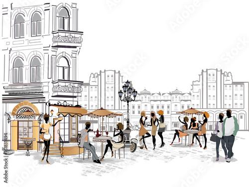 Dziewczyny mody w kawiarni ulicy. Uliczna kawiarnia z kwiatami w starym mieście. Kelnerzy obsługują stoły.