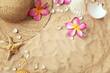 summer hat and seashells on sand, summer background