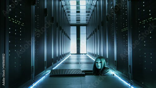 Fotografía  Hooded Hacker in a Mask Watching From Under Floor Hatch in Data Center with Rows of Rack Servers