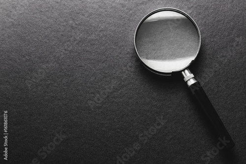 Photo magnifying glass on  black texture  background.
