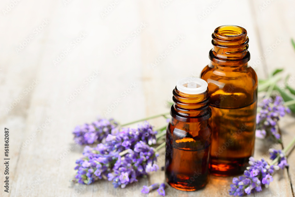 Fototapety, obrazy: Lavender essential oil in the amber bottle, on the wooden table