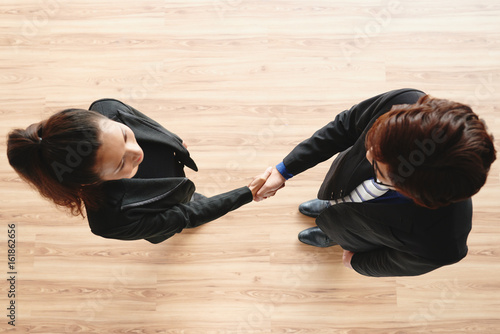 Confident business partners greeting each other with firm handshake while standi Poster