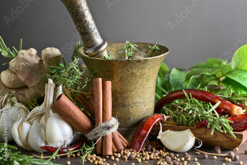 Fotografia  Different herbs and spices on a wooden table .