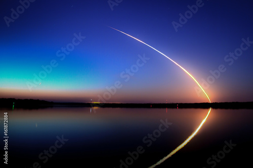 Photo Space Shuttle Launch into a blue sky at dawn with reflection on the water