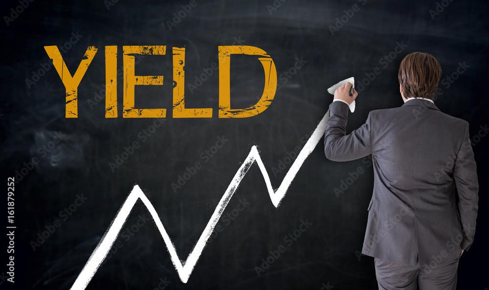 Fototapety, obrazy: Businessman writes YIELD on blackboard concept