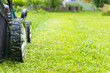 canvas print picture - Mowing lawns, Lawn mower on green grass, mower grass equipment, mowing gardener care work tool, close up view, sunny day