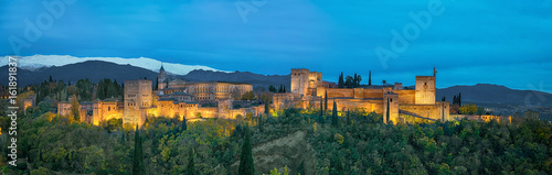 Panorama of Alhambra - medieval Moorish fortress surrounded by yellow autumn trees illuminated in the evening, Granada, Andalusia, Spain