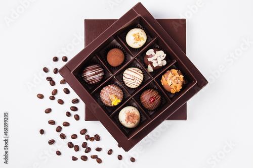 Plakat ręcznie robione czekoladki w kwadratowym pudełku i ziaren kawy w pobliżu (widok z góry)