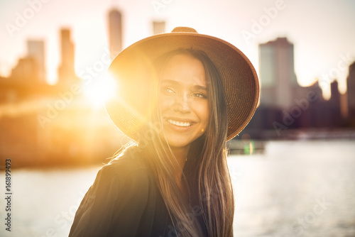 Close-up portrait of beautiful smiling woman looking to the side on the beach in city.