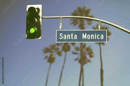 Fotografie, Obraz  Retro styled Santa Monica Boulevard road sign with defocused palm trees in backg