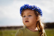 Leinwanddruck Bild - Little girl in a wreath of cornflowers