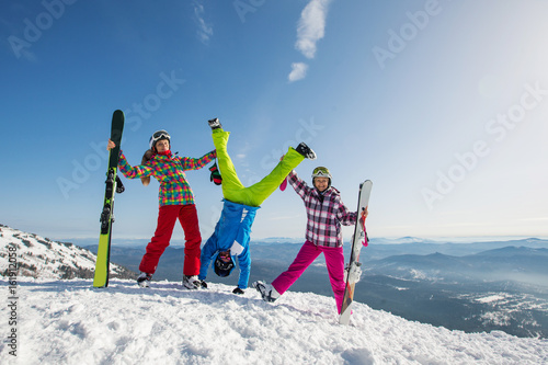 Happy friends having fun playing in snow, Man standing on his hands. Ski and snowboard holiday