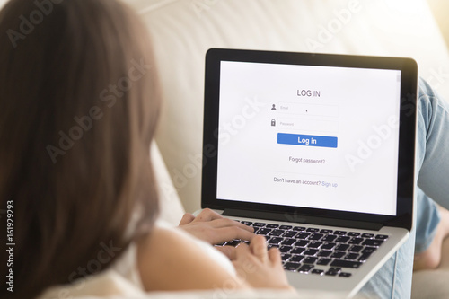 Cuadros en Lienzo Woman lying on sofa with laptop enters email and password on web verification page