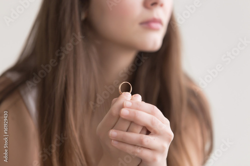 Close up photo of golden ring in womans hands  Lonely young lady