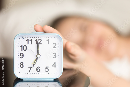 Photo  Close up picture of square alarm clock on bedside table showing seven o'clock AM with blurred person in bed reaching hand to turn off the awake signal sound