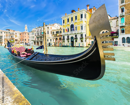 Photo sur Toile Gondoles Tourists travel on gondolas at canal Venice, Italy . Gondola trip is the most popular touristic activity in Venice.