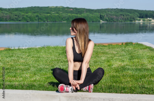 Slim girl sitting on the grass on the shore of the lake. Fitness on the coast.