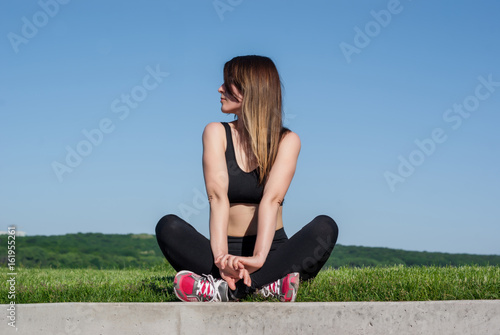 Staande foto Ontspanning Slim girl sitting on the grass on the shore of the lake. Fitness on the coast.