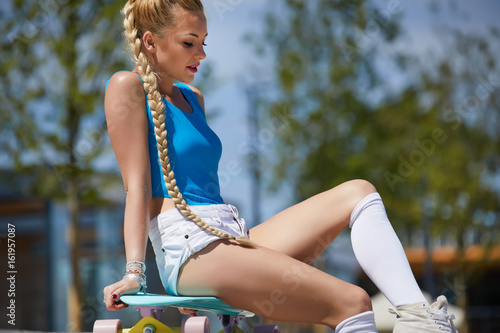 Photo  Beautiful and sexy girl sitting on the skateboard