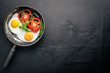 Fried egg with herbs and vegetables in a frying pan. Top view. Free space.