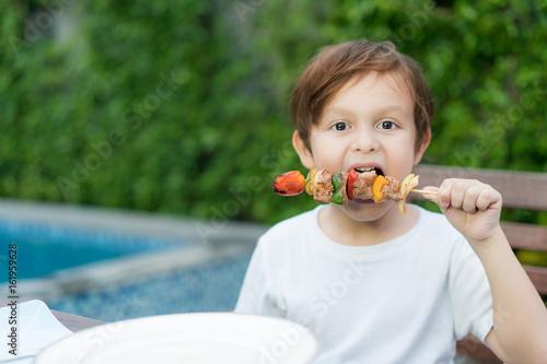 Plakat Śliczny chłopiec łasowanie piec na grillu grill w domu.