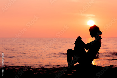 Poster Corail Woman silhouette sitting on sunset sea background, side view, back lit
