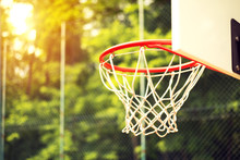 Junior Basketball Hoop In Park Surrounded By Wire Fence