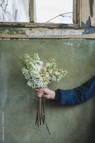 Junge hält selbst gepflückte Blumen in der Hand vor der Wand eines sehr alten Gebäudes