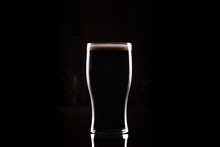 Stout (Guinness Like) Beer In Pint Glass, Silhouette With Perfect Head And Dark Background