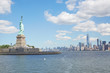 Statue of Liberty island and New York city skyline in a sunny day, white clouds