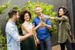 Friends having outdoor garden party toast with alcoholic cider drinks