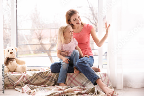 Mother and daughter sitting on windowsill