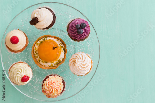 Photo  Top view on homemade vanilla, blueberry, lemon, chocolate cupcakes on cristal plate on turquoise retro wooden background