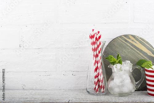 Zdjęcie XXL Kuchnia martwa natura biały mur: przybory kuchenne, deska do krojenia, kostki lodu na koktajle, jagody, rurki koktajlowe na wakacje na podwórku. W poziomie