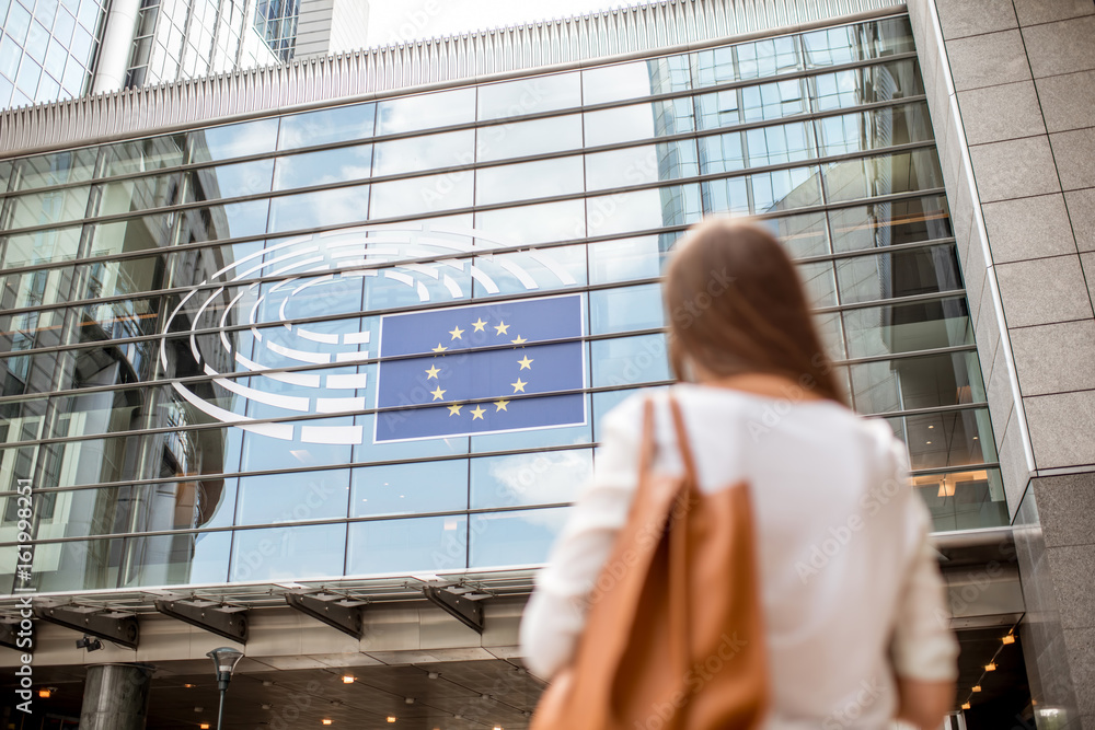 Fototapety, obrazy: Young businesswoman standing back near the Parliament building of European Union in Brussel city