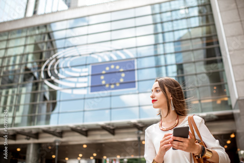 Foto  Young businesswoman standing with phone near the Parliament building of European