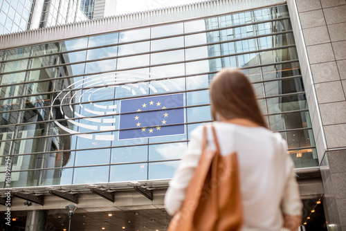 Foto  Young businesswoman standing back near the Parliament building of European Union