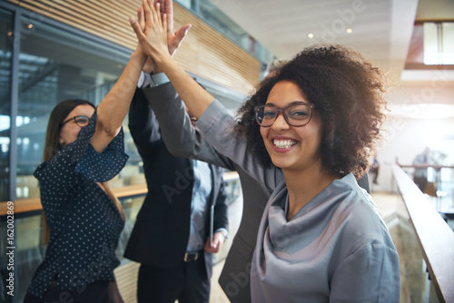 Smiling black businesswoman giving high five to ofiice team Canvas Print