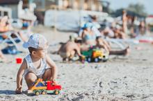 Child Playing On A Sandy Beach Near The Sea