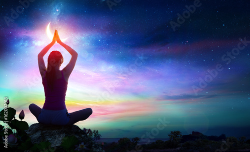 Fotografering Woman Doing Yoga With Lotus Flowers And Chakra Gradient Colors - Spiritual Conte