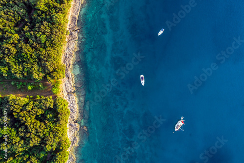 Coastal area with three boats on blue clear water and forest on land - aerial view taken by drone